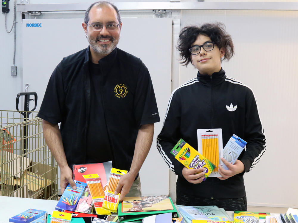 The Senior Times' volunteer Prospero Monroy Demesa (right) delivers school supplies to Sun Youth's Nicolas Carpentier August 29 to fulfill the needs of children on the waiting list.